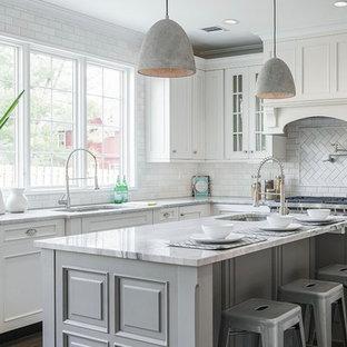 Große Klassische Küche in L-Form mit Unterbauwaschbecken, Glasfronten, weißen Schränken, Küchenrückwand in Weiß, Rückwand aus Metrofliesen, dunklem Holzboden, Kücheninsel, braunem Boden und grauer Arbeitsplatte in New York