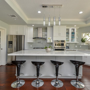 This is an example of a mid-sized modern kitchen in Houston with a single-bowl sink, shaker cabinets, white cabinets, quartz benchtops, grey splashback, glass tile splashback, stainless steel appliances, medium hardwood floors, with island and red floor.