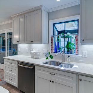 アトランタの中サイズのトラディショナルスタイルのおしゃれなキッチン (アンダーカウンターシンク、シェーカースタイル扉のキャビネット、白いキャビネット、珪岩カウンター、白いキッチンパネル、サブウェイタイルのキッチンパネル、シルバーの調理設備の、コルクフローリング) の写真