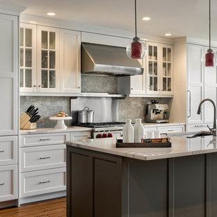 Klassisk inredning av ett stort kök, med en undermonterad diskho, skåp i shakerstil, vita skåp, grått stänkskydd, rostfria vitvaror, mellanmörkt trägolv, en köksö, bänkskiva i kvarts och stänkskydd i kalk