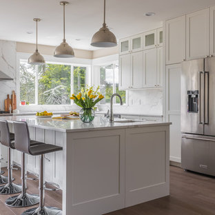 Inspiration for a large transitional l-shaped medium tone wood floor and brown floor kitchen remodel in Seattle with an undermount sink, shaker cabinets, white cabinets, granite countertops, white backsplash, stone slab backsplash, stainless steel appliances, an island and white countertops