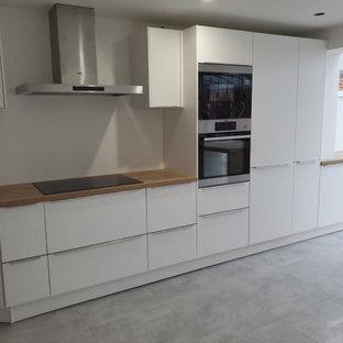 カーディフの中サイズのモダンスタイルのおしゃれなキッチン (ダブルシンク、フラットパネル扉のキャビネット、白いキャビネット、ラミネートカウンター、シルバーの調理設備の、セラミックタイルの床、グレーの床、茶色いキッチンカウンター) の写真