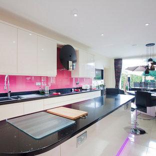 他の地域の大きいおしゃれなキッチン (ダブルシンク、フラットパネル扉のキャビネット、白いキャビネット、人工大理石カウンター、ピンクのキッチンパネル、ガラス板のキッチンパネル、パネルと同色の調理設備、セラミックタイルの床、白い床) の写真