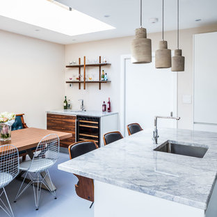 Medium sized contemporary l-shaped open plan kitchen in Oxfordshire with flat-panel cabinets, white cabinets, grey floors, stainless steel appliances, a single-bowl sink, granite worktops, metallic splashback, ceramic flooring and a breakfast bar.