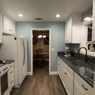 Small transitional enclosed kitchen designs - Small transitional galley vinyl floor enclosed kitchen photo in Other with an undermount sink, flat-panel cabinets, white cabinets, granite countertops and white appliances