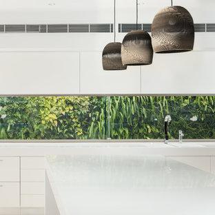 サンシャインコーストのトロピカルスタイルのおしゃれなアイランドキッチン (フラットパネル扉のキャビネット、白いキャビネット、ガラス板のキッチンパネル) の写真