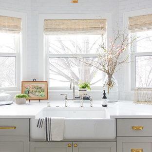ミネアポリスの広いトランジショナルスタイルのおしゃれなキッチン (エプロンフロントシンク、レイズドパネル扉のキャビネット、グレーのキャビネット、大理石カウンター、白いキッチンパネル、レンガのキッチンパネル、シルバーの調理設備、無垢フローリング、茶色い床、白いキッチンカウンター) の写真