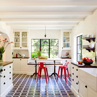 Mediterranean enclosed kitchen photos - Inspiration for a mediterranean galley enclosed kitchen remodel in Portland with a farmhouse sink, shaker cabinets, white cabinets, wood countertops, white backsplash, subway tile backsplash and stainless steel appliances
