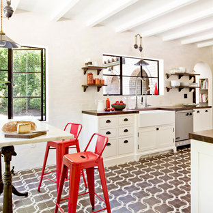 Example of a tuscan eat-in kitchen design in Portland with a farmhouse sink, shaker cabinets, white cabinets, wood countertops, white backsplash, subway tile backsplash and stainless steel appliances
