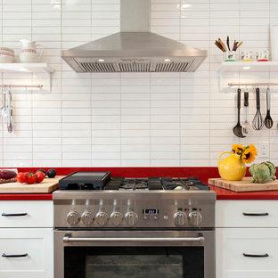 На фото: кухня в скандинавском стиле с обеденным столом, врезной раковиной, фасадами в стиле шейкер, белыми фасадами, столешницей из кварцевого композита, белым фартуком, фартуком из керамической плитки, техникой из нержавеющей стали, полом из керамогранита, полуостровом и красной столешницей с