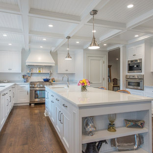 This is an example of a large traditional l-shaped eat-in kitchen in New York with an undermount sink, beaded inset cabinets, white cabinets, glass benchtops, stainless steel appliances, medium hardwood floors and with island.