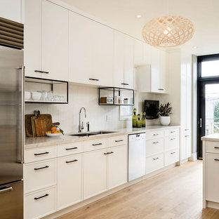 Diseño de cocina de galera, contemporánea, grande, abierta, con puertas de armario blancas, salpicadero blanco, electrodomésticos de acero inoxidable, fregadero de doble seno, armarios estilo shaker, encimera de acrílico, salpicadero de azulejos de porcelana y suelo de madera clara