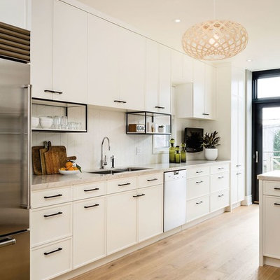 Open concept kitchen - large contemporary galley light wood floor open concept kitchen idea in San Francisco with white cabinets, white backsplash, stainless steel appliances, a double-bowl sink, shaker cabinets, solid surface countertops and porcelain backsplash