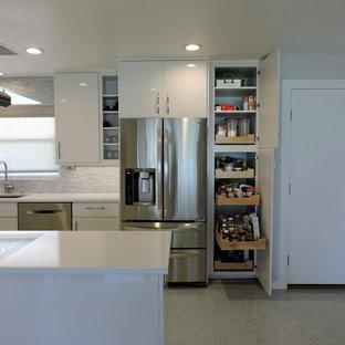 タンパの中くらいのコンテンポラリースタイルのおしゃれなキッチン (アンダーカウンターシンク、フラットパネル扉のキャビネット、白いキャビネット、御影石カウンター、白いキッチンパネル、石タイルのキッチンパネル、シルバーの調理設備、クッションフロア) の写真