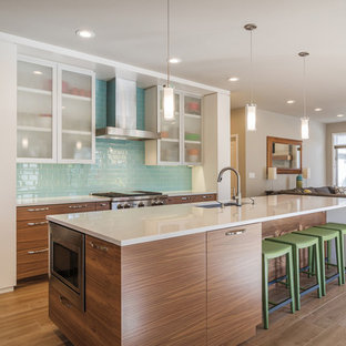 Contemporary kitchen inspiration - Inspiration for a contemporary galley brown floor kitchen remodel in Chicago with an undermount sink, flat-panel cabinets, dark wood cabinets, blue backsplash, glass tile backsplash, stainless steel appliances and an island