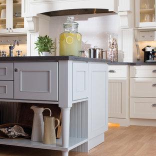 アトランタのエクレクティックスタイルのおしゃれなキッチン (エプロンフロントシンク、シェーカースタイル扉のキャビネット、白いキャビネット、人工大理石カウンター、白いキッチンパネル、サブウェイタイルのキッチンパネル、シルバーの調理設備の、淡色無垢フローリング) の写真