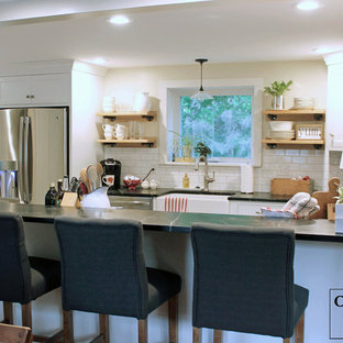 Mid-sized shabby-chic style galley eat-in kitchen in New York with a farmhouse sink, recessed-panel cabinets, white cabinets, soapstone benchtops, white splashback, subway tile splashback, stainless steel appliances, slate floors and a peninsula.