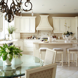 Victorian eat-in kitchen designs - Ornate u-shaped beige floor eat-in kitchen photo in New York with recessed-panel cabinets, beige cabinets, beige backsplash, stainless steel appliances and an island