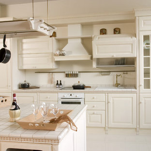 This is an example of a large country single-wall open plan kitchen in Montreal with a double-bowl sink, beaded inset cabinets, white cabinets, tile benchtops, white splashback, vinyl floors and with island.
