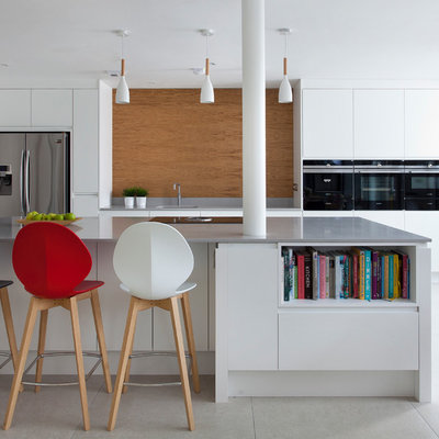 Example of a trendy galley gray floor open concept kitchen design in Other with an undermount sink, flat-panel cabinets, white cabinets, brown backsplash, stainless steel appliances, an island and gray countertops