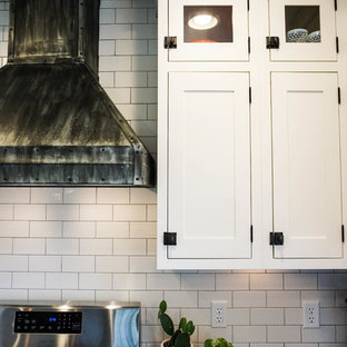 Small rural u-shaped kitchen pantry in Columbus with a built-in sink, shaker cabinets, white cabinets, white splashback, metro tiled splashback, stainless steel appliances, dark hardwood flooring, an island, brown floors and zinc worktops.