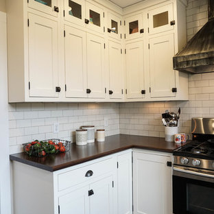 Design ideas for a small rural u-shaped kitchen pantry in Columbus with a built-in sink, shaker cabinets, white cabinets, white splashback, metro tiled splashback, stainless steel appliances, dark hardwood flooring, an island, brown floors and zinc worktops.
