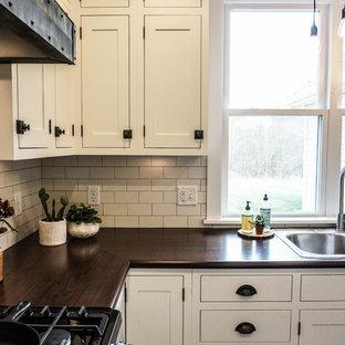 Esempio di una piccola cucina country con lavello da incasso, ante in stile shaker, ante bianche, paraspruzzi bianco, paraspruzzi con piastrelle diamantate, elettrodomestici in acciaio inossidabile, parquet scuro, isola, pavimento marrone e top in zinco