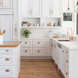 Example of a large french country l-shaped light wood floor open concept kitchen design in St Louis with an undermount sink, recessed-panel cabinets, white cabinets, quartzite countertops, white backsplash, subway tile backsplash, paneled appliances and an island