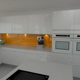 ドーセットの広いモダンスタイルのおしゃれなキッチン (アンダーカウンターシンク、フラットパネル扉のキャビネット、白いキャビネット、ステンレスカウンター、オレンジのキッチンパネル、ガラス板のキッチンパネル、白い調理設備、磁器タイルの床) の写真