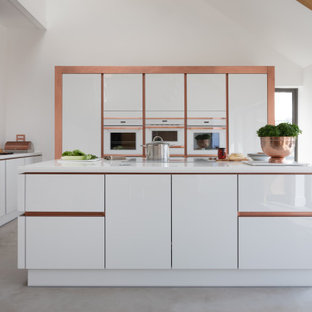 Inspiration for a contemporary u-shaped open plan kitchen in Other with a submerged sink, flat-panel cabinets, white cabinets, white splashback, integrated appliances, concrete flooring, an island, grey floors and white worktops.
