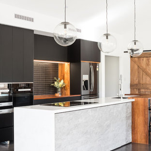 Inspiration for a mid-sized contemporary galley open plan kitchen in Hobart with an undermount sink, black cabinets, solid surface benchtops, black splashback, ceramic splashback, stainless steel appliances, concrete floors, with island, grey floor, white benchtop and flat-panel cabinets.