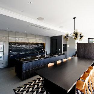 Exemple d'une grand cuisine américaine parallèle tendance avec un évier encastré, un placard à porte plane, des portes de placard grises, un plan de travail en marbre, une crédence noire, une crédence en dalle de pierre, un sol en carrelage de porcelaine, un îlot central, un électroménager en acier inoxydable et un plan de travail noir.