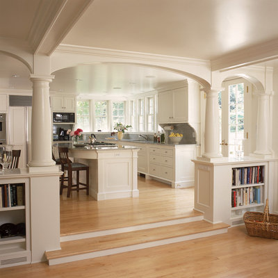 Elegant open concept kitchen photo in New York with recessed-panel cabinets, white cabinets and paneled appliances