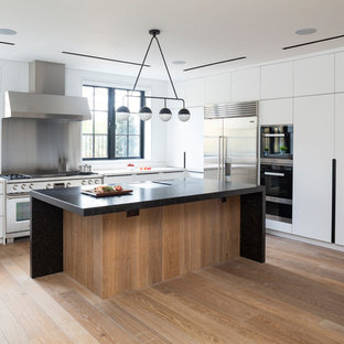 Inspiration for a contemporary l-shaped kitchen in London with flat-panel cabinets, white cabinets, metallic splashback, stainless steel appliances, light hardwood flooring, an island and white worktops.