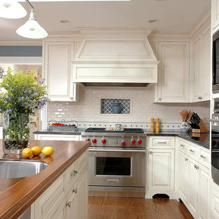 Mid-sized elegant kitchen photo in Chicago with stainless steel appliances, wood countertops, an undermount sink, raised-panel cabinets, white backsplash and subway tile backsplash