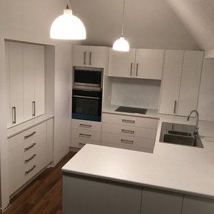 クライストチャーチの小さいコンテンポラリースタイルのおしゃれなキッチン (ダブルシンク、フラットパネル扉のキャビネット、白いキャビネット、ラミネートカウンター、白いキッチンパネル、ガラス板のキッチンパネル、シルバーの調理設備の、クッションフロア、アイランドなし、茶色い床) の写真