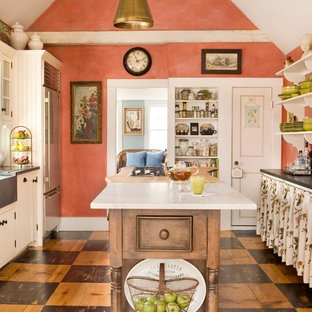 Country separate kitchen in Los Angeles with a farmhouse sink, louvered cabinets, white cabinets, multi-coloured splashback, stainless steel appliances, with island and brown floor.