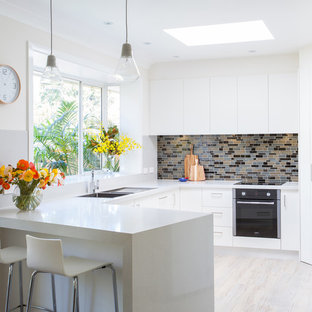 Photo of a mid-sized contemporary l-shaped eat-in kitchen in Other with flat-panel cabinets, white cabinets, with island, an undermount sink, quartz benchtops, grey splashback, glass tile splashback, stainless steel appliances and medium hardwood floors.