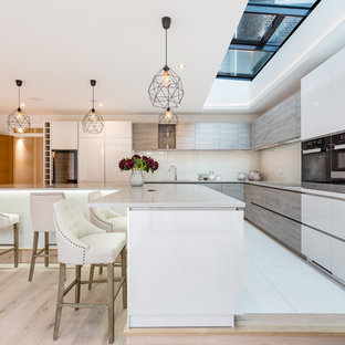Photo of a large contemporary l-shaped kitchen in London with a built-in sink, flat-panel cabinets, white cabinets, engineered stone countertops, beige splashback, ceramic splashback, ceramic flooring, an island and white floors.