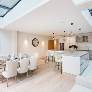 Design ideas for a large contemporary l-shaped kitchen/diner in London with a built-in sink, flat-panel cabinets, white cabinets, engineered stone countertops, beige splashback, ceramic splashback, black appliances, ceramic flooring, an island and white floors.