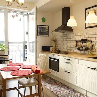 Пример оригинального дизайна: маленькая угловая кухня в скандинавском стиле с обеденным столом, фасадами с выступающей филенкой, белыми фасадами, столешницей из ламината, белым фартуком, белой техникой, паркетным полом среднего тона, двойной раковиной и фартуком из плитки кабанчик без острова