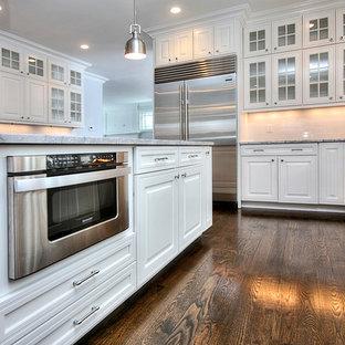 Offene, Mittelgroße Klassische Küche in L-Form mit Unterbauwaschbecken, profilierten Schrankfronten, weißen Schränken, Marmor-Arbeitsplatte, Küchenrückwand in Weiß, Rückwand aus Porzellanfliesen, Küchengeräten aus Edelstahl, dunklem Holzboden und Kücheninsel in New York
