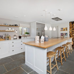 Design ideas for a coastal kitchen in Devon with a submerged sink, shaker cabinets, white cabinets, wood worktops, stainless steel appliances, an island, grey floors, beige worktops and slate flooring.