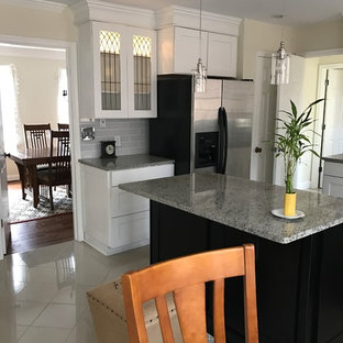 This is an example of a small traditional u-shaped eat-in kitchen in DC Metro with an undermount sink, glass-front cabinets, white cabinets, granite benchtops, white splashback, glass tile splashback, stainless steel appliances, ceramic floors, with island and beige floor.