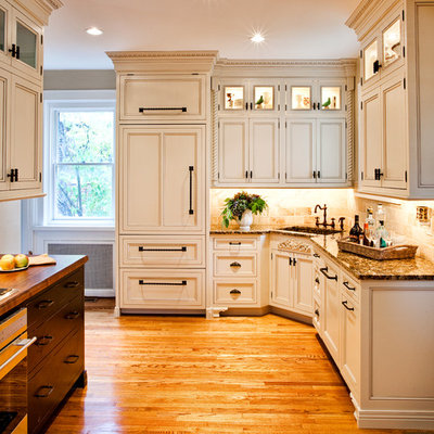Mid-sized elegant l-shaped medium tone wood floor enclosed kitchen photo in St Louis with an integrated sink, recessed-panel cabinets, beige cabinets, beige backsplash, paneled appliances, granite countertops, stone tile backsplash and a peninsula