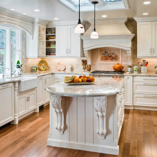 Design ideas for a traditional u-shaped eat-in kitchen in San Francisco with a farmhouse sink, recessed-panel cabinets, white cabinets, beige splashback, porcelain splashback and stainless steel appliances.