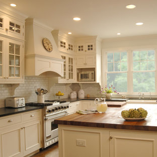 Traditional kitchen designs - Example of a classic kitchen design in Chicago with soapstone countertops and white appliances