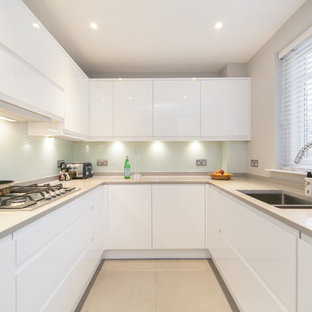 This is an example of a contemporary u-shaped kitchen in London with a double-bowl sink, flat-panel cabinets, white cabinets, quartz benchtops, glass sheet splashback, ceramic floors and no island.