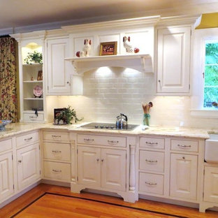 Mid-sized traditional open concept kitchen photos - Example of a mid-sized classic l-shaped medium tone wood floor open concept kitchen design in New York with a farmhouse sink, raised-panel cabinets, white cabinets, granite countertops, white backsplash, subway tile backsplash, white appliances and a peninsula