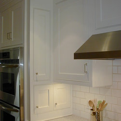White Kitchen w/ Butler Pantry - Rather than add a spice drawer or use space within a wall cabinet, we sometimes mount a shallow spice cabinet to the side of an oven or refrigerator cabinet, thus utilizing little space and adding storage for small items that shouldn't be hidden.